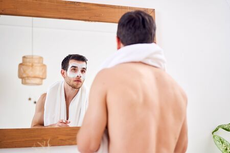 Brunet male with white mask on his face standing in bath opposite mirror Foto de archivo