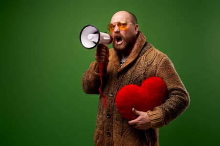 Man in orange glasses with toy heart and bullhorn in his hands on empty green background Stok Fotoğraf