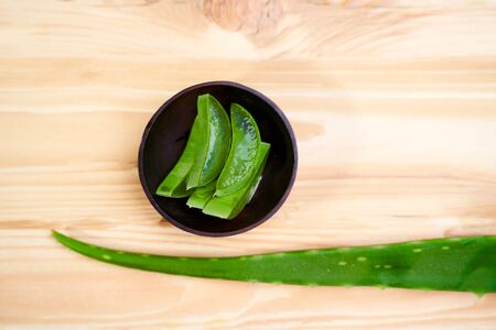 Aloe vera in cup on empty wooden table, close-up