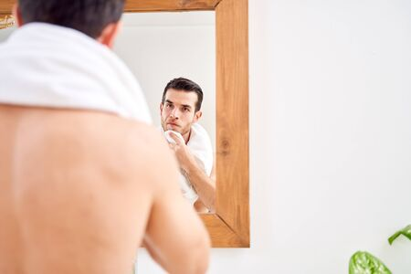 Young male wipes his towel while standing by mirror in bath in morning. Stockfoto