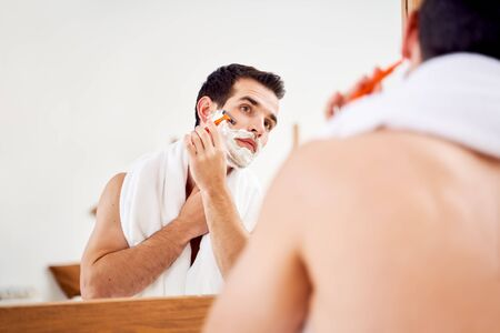 Young male with foam on his beard shaves near mirror in morning