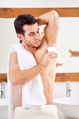 Brunet male applies deodorant to armpits while standing in bath opposite mirror