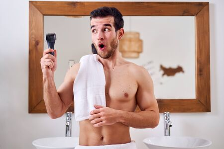 Surprised male with electric razor in hand with towel on his shoulder stands near mirror in bath Stock fotó