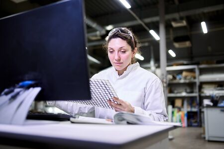 Young woman lab technician sitting at table with computer and carbon mesh Stock Photo