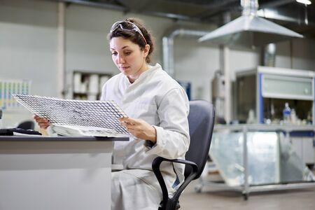 Young woman lab technician sitting at table with carbon mesh Banque d'images