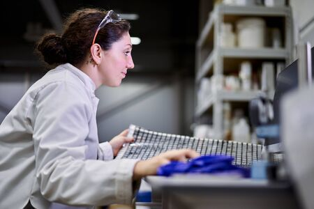 Side view woman in white coat with carbon mesh sits on table in laboratory