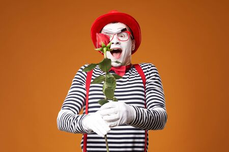 Happy mime man in red hat, glasses and vest with rose in hands on orange background