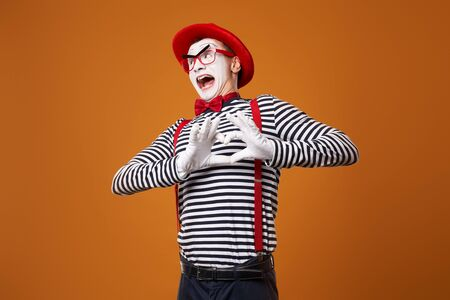 Mime man in vest and red hat with heart made of palms on orange background