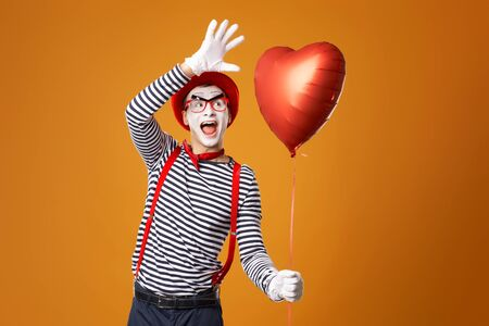 Happy mime male in red hat and vest holds heart ball in his hands on empty orange background 版權商用圖片