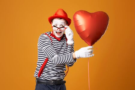 Clown mime with heart ball on orange background 版權商用圖片
