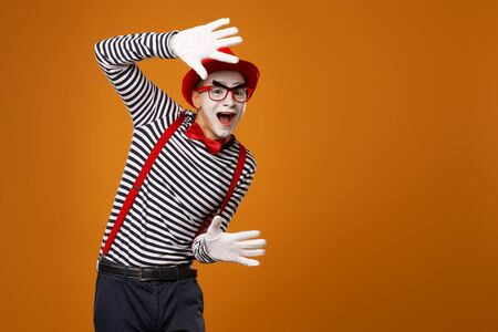 Smiling mime man in red hat, white gloves and striped t-shirt on blank orange background in studio.