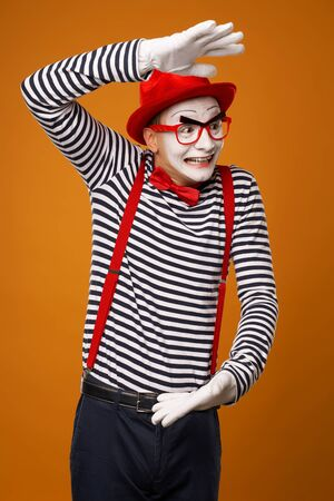 Surprised mime with white face in red hat and striped t-shirt on blank orange background Stock Photo