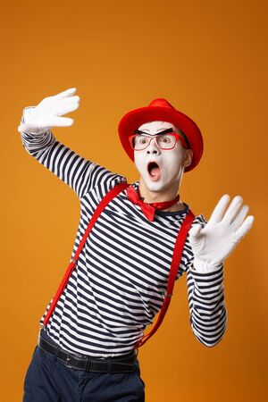 Young mime male in white gloves and red hat looking at side on orange background
