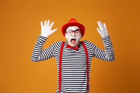 Surprised mime clown in red hat and in vest with hands up on orange background