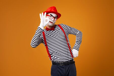 Mime man in vest and red hat Isolated on orange background