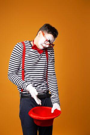 Trauriger Pantomime in Weste mit leerem roten Hut isoliert auf orangem Hintergrund