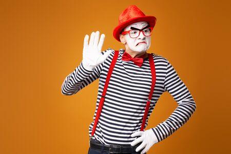 Trauriger Pantomime in rotem Hut und Weste auf leerem orangefarbenem Hintergrund