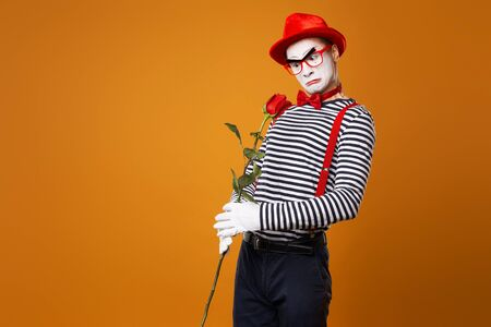 Unhappy mime man with white face in red hat and striped t-shirt holding rose on empty orange background