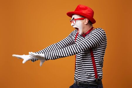 Dissatisfied mime in vest and red hat on orange background