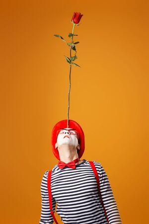 Pantomime in Weste und rotem Hut, der mit Rose auf seiner Stirn isoliert aufschaut