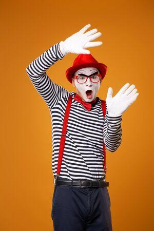Überraschter Pantomime in Weste und rotem Hut auf orangem Hintergrund isoliert
