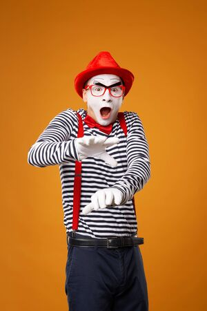 Young mime man looking at camera in vest and red hat Isolated on orange background