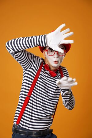 Serious mime in white gloves and red hat looking at camera on orange background