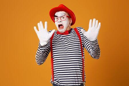 Trauriger Pantomime mit rotem Hut und Weste mit erhobenen Händen auf orangefarbenem Hintergrund