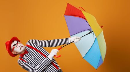 Mime with multi-colored umbrella during wind isolated on empty orange background