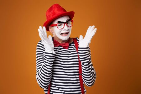 Young mime man in red hat and vest on orange background