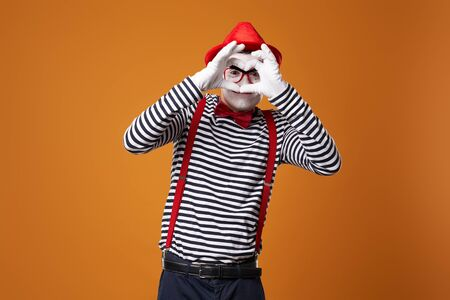Mime in vest and red hat with heart made of palms on orange background