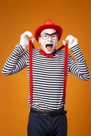 Happy mime looking at camera in vest and red hat Isolated on orange background Standard-Bild