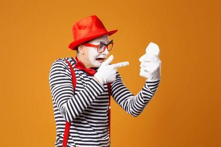 Trauriger Pantomime mit rotem Hut und Weste mit weißer Maske auf orangem Hintergrund Standard-Bild