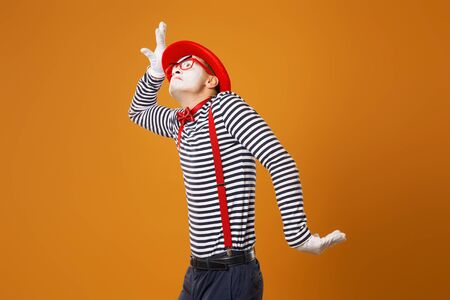 Mime male in red hat and in vest pointing on orange background