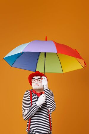 Dissatisfied mime with multi-colored umbrella isolated on blank orange background