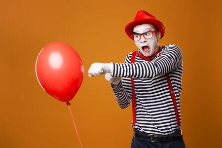 Sad clown mime box with red ball on orange background Standard-Bild