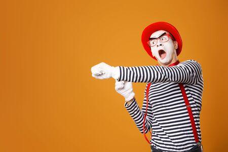Trauriger Clown Pantomime in rotem Hut und Weste auf orangem Hintergrund