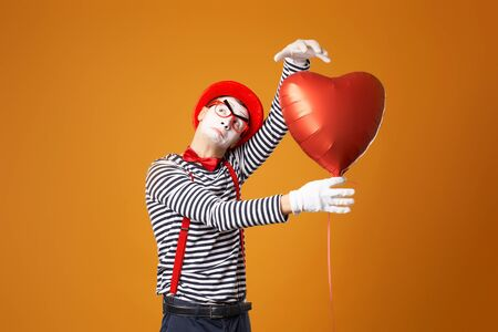 Serious clown mime male in red hat and vest holds heart ball in his hands