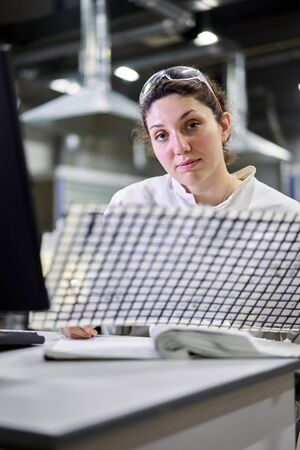 Woman in white coat with carbon mesh sits on table in laboratory