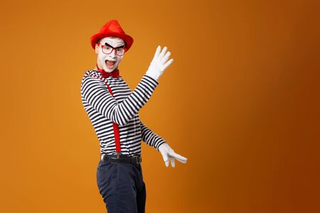 Pantomime in weißen Handschuhen und rotem Hut, der auf orangefarbenem Hintergrund in die Kamera schaut Standard-Bild