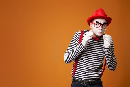 Pensive mime man in red hat, white gloves and striped t-shirt on blank orange background