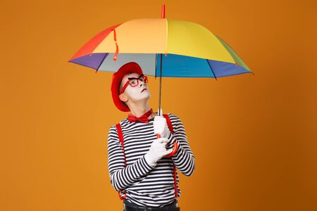 Mime looking up with multi-colored umbrella in hand isolated on blank orange background
