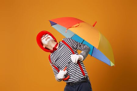 Mime man looking up with multi-colored umbrella in hand isolated on blank orange background