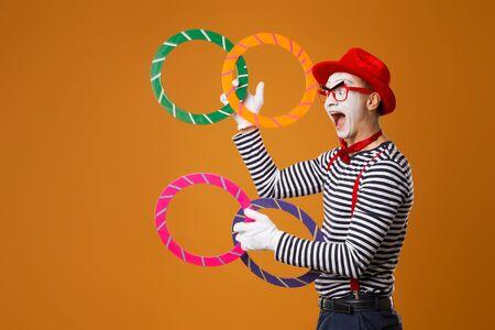 Fröhlicher Pantomime mit bunten Ringen auf orangem Hintergrund