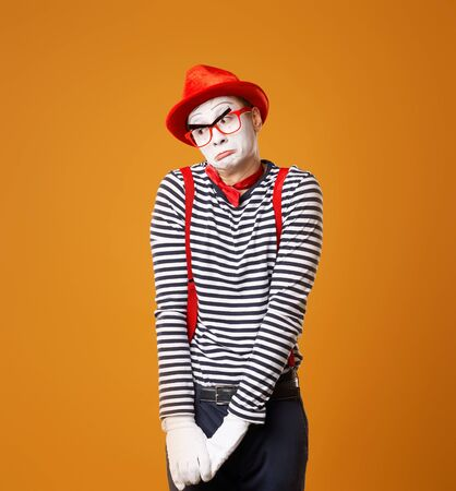 Upset mime man in red hat and vest on orange background