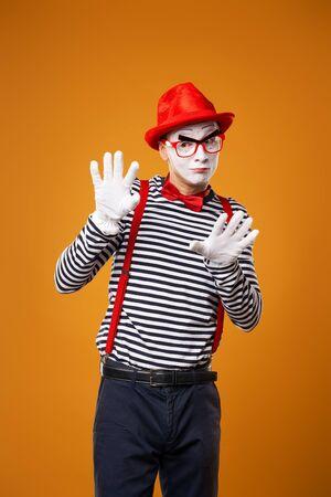 Pantomime mit Blick in die Kamera in Weste und rotem Hut auf orangem Hintergrund isoliert