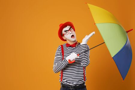 One mime with multi-colored umbrella on empty orange background Stok Fotoğraf