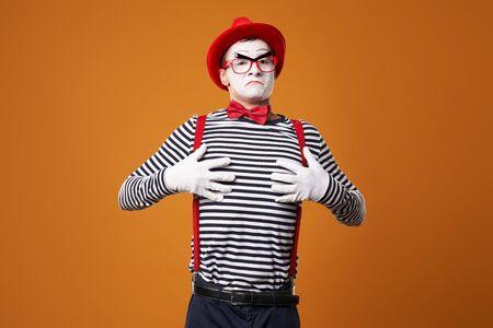 Pantomime in Weste und rotem Hut auf orangem Hintergrund