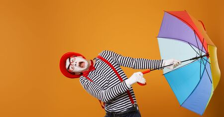 Mime man with multi-colored umbrella during wind isolated on empty orange background Banco de Imagens