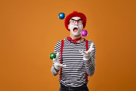 Mime in vest and red hat juggles with colorful balls on orange background